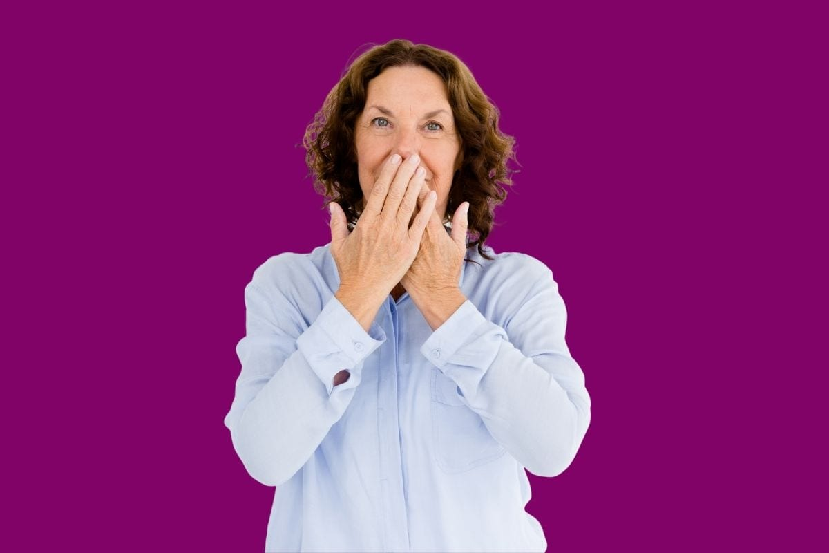 Woman covering mouth to hide denture